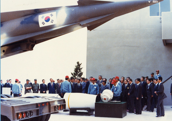 Immediately after the successful launch of Korea's first surface-to-surface missile Baekgom at Anheung Test Site in South Chungcheong Province on September 26, 1978, President Park Chung-hee listens to an explanation of the fuselage from officials at the National Defense Science Research Institute next to the missile.  JoongAng Photo