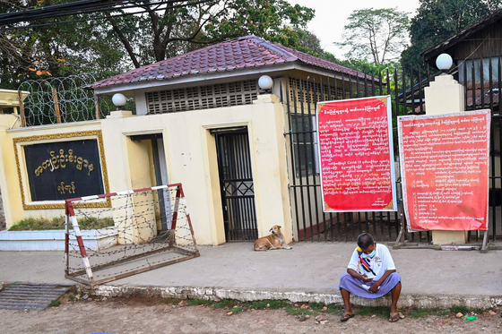 A man sits in front of Insein Prison.  AFP=Yonhap News