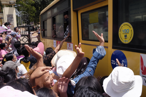 In April, when the Myanmar military government released 23,000 prisoners in Insein prison for the New Year holidays, citizens are waving their hands toward the bus leaving the prison.  AP=Yonhap News