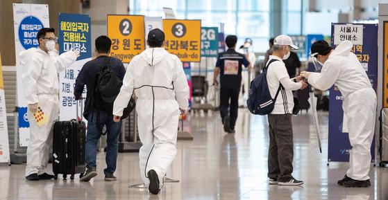 인천국제공항 검역소 관련 신종 코로나바이러스 감염증(코로나19) 확진자 15명이 인도발 변이 바이러스 감염으로 확인된 가운데 20일 인천국제공항 제1여객터미널 입국장에서 방역관계자들이 입국자들을 안내하고 있다. 뉴스1
