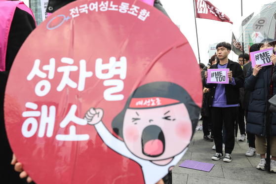 2018년 3월 8일 세계여성의날에 서울 종로구 광화문광장에서 열린 3 전국여성노동자대회에서 참가자들이 성별임금격차 해소를 촉구하는 손팻말과 미투 운동에 동참하는 손팻말을 들고 있다. 뉴스1