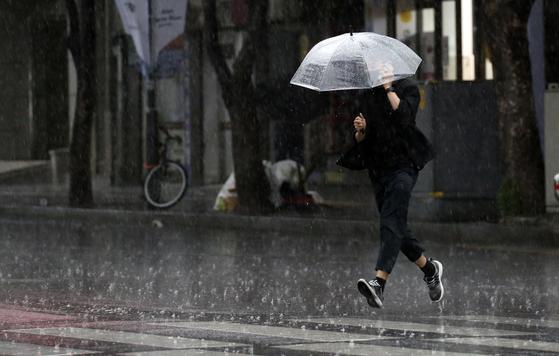 지난달 28일 오후 울산 남구 한 거리에서 우산을 쓴 시민이 뛰어가고 있다. 뉴스1