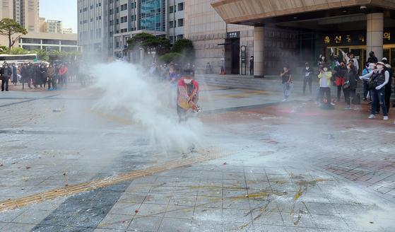 지난달 24일 오후 울산시청 앞에서 열린 유흥업소 업주들의 집회에서 한 참석자가 밀가루를 뿌리고 있다. 업주들은 울산시에 집합 금지 중단과 휴업에 따른 보상을 요구했다. 연합뉴스