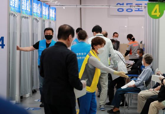 정부가 6월 말부터 신종 코로나바이러스 감염증(코로나19) 백신을 접종한 65세 이상에게 접종을 증명하는 '백신 접종 스티커'를 나눠줄 계획이다. 사진은 4일 서울 영등포아트홀에 마련된 코로나19 예방접종센터에서 백신 접종을 안내하는 의료진과 직원의 모습. 뉴스1