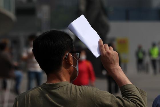 6일 오전 서울 중구 서울역 광장 임시선별검사소에서 한 시민이 신종 코로나바이러스 감염증(코로나19) 검사를 받기 위해 대기하던 중 종이로 햇볕을 가리고 있다. 뉴스1
