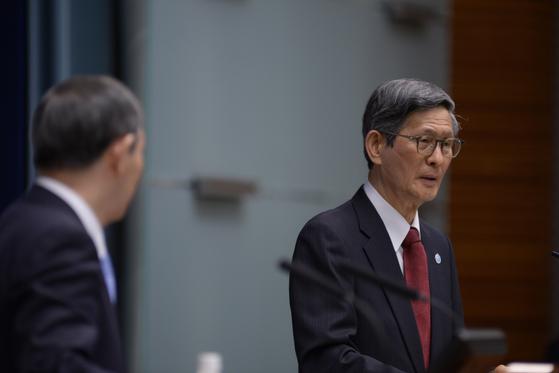 지난달 7일 열린 기자회견에서 스가 요시히데 일본 총리(왼쪽)의 옆에서 코로나19 상황을 설명하고 있는 오미 시게루 코로나19 정부대책분과회 회장. [AP=연합뉴스]