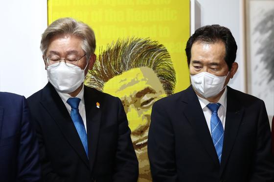 이재명 경기지사(왼족)과 정세균 전 국무총리(오른쪽)가 지난달 19일 서울 종로구 인사동 마루아트센터에서 열린 노무현 서거 12주기 추모전시에 참석해 캘리그라피 퍼포먼스를 보고 있다. 오종택 기자