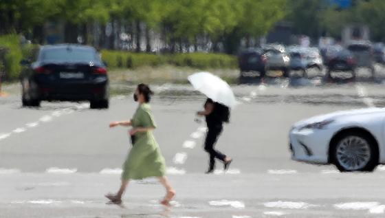 한여름 더위를 보인 8일 오후 광주 광산구 수완지구에서 시민들이 햇볕에 달궈져 열기를 내뿜는 도로를 건너고 있다. 연합뉴스