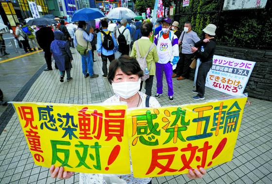 """6일 일본 도쿄에서 한 시민이 """"감염 올림픽에 반대한다""""고 적힌 피켓을 들고 시위를 하고 있다. [EPA=연합뉴스]"""