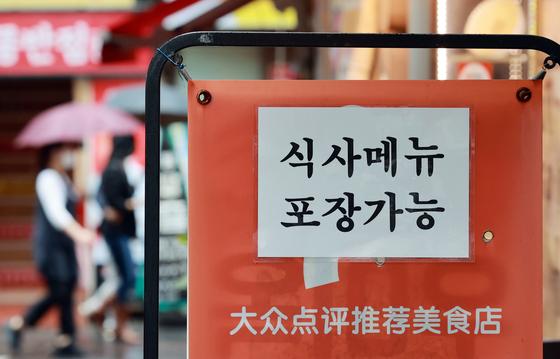 지난달 21일 서울 중구 명동의 한 식당 앞에 식사 메뉴 포장 안내문이 부착돼 있다. 연합뉴스