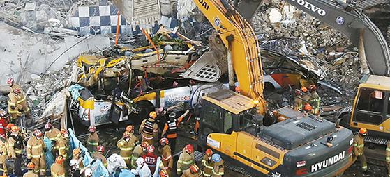 9일 오후 철거 중인 건물 붕괴로 시내버스가 매몰된 광주광역시 사고 현장에서 소방대원들이 구조 작업을 하고 있다. 이 사고로 9명이 사망하고 8명이 부상했다. [연합뉴스]