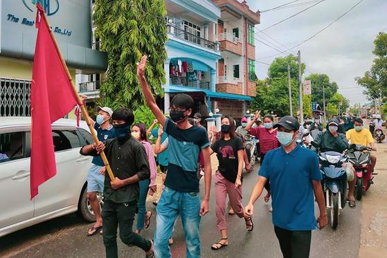 군부 쿠데타 반대하는 시위대가 세 손가락을 펴고 행진하고 있다. AFP 연합뉴스