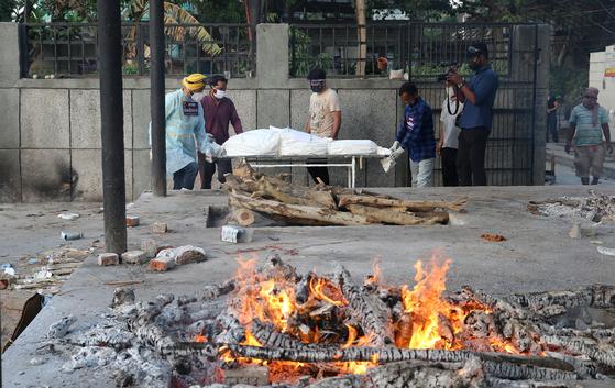 인도의 하루 코로나19 관련 사망자 수가 3000명대를 기록하던 지난달 12일 인도의 뉴델리에서 자원봉사자가 코로나19 사망자를 옮기고 있다. [EPA=연합뉴스]