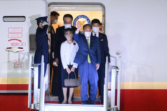 스가 요시히데 일본 총리가 11일 G7 참석을 위해 영국 콘월 공항에 도착한 후 손을 흔들고 있다. [AFP=연합뉴스]