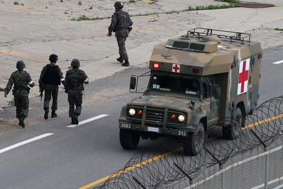 [2014년 6월 23일 강원도 고성군 현내면 마차진리 야산에서 육군 22사단 GOP(일반전초) 총기 난사 탈영병 임모 병장이 군병력과 대치하다 자살을 시도한 가운데 임 병장을 태운 군 구급차량이 이동하고 있다. 뉴스1