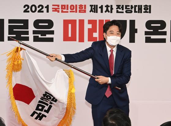 이준석 국민의힘 대표가 지난 11일 오전 서울 영등포구 여의도동 국민의힘 당사에서 열린 전당대회에서 당기를 흔들고 있다. 오종택 기자