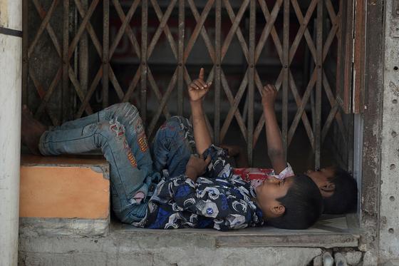 신종 코로나바이러스 감염증(코로나19)이 확산되고 있는 가운데 지난 5월16일 인도 뉴델리의 한 폐쇄된 상점 앞에서 아이들이 쉬고 있다. AFP=연합뉴스