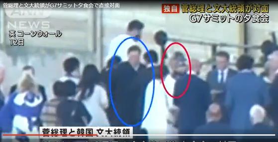 일본 방송 ANN이 공개한 영상 속에서 만찬에 참석한 문재인 대통령(파란 원)이 스가 총리(빨간 원)와 인사를 나누는 모습. [사진 ANN 방송화면 캡처]