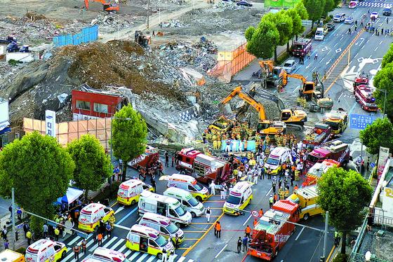 지난 9일 철거 중인 건물 붕괴로 시내버스가 매몰된 광주광역시 사고 현장에서 소방대원들이 구조 작업을 하고 있다. 이 사고로 9명이 사망하고, 8명이 부상했다. 프리랜서 장정필