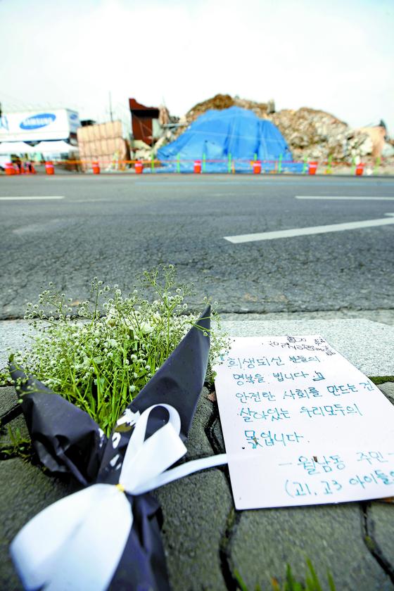 13일 광주 철거건물 붕괴사고 현장 인근에 꽃다발과 손편지가 놓여있다. 이날까지 희생자 9명 중 7명의 발인이 이뤄졌고, 오늘(14일) 마지막 2명의 발인이 진행된다. [연합뉴스]