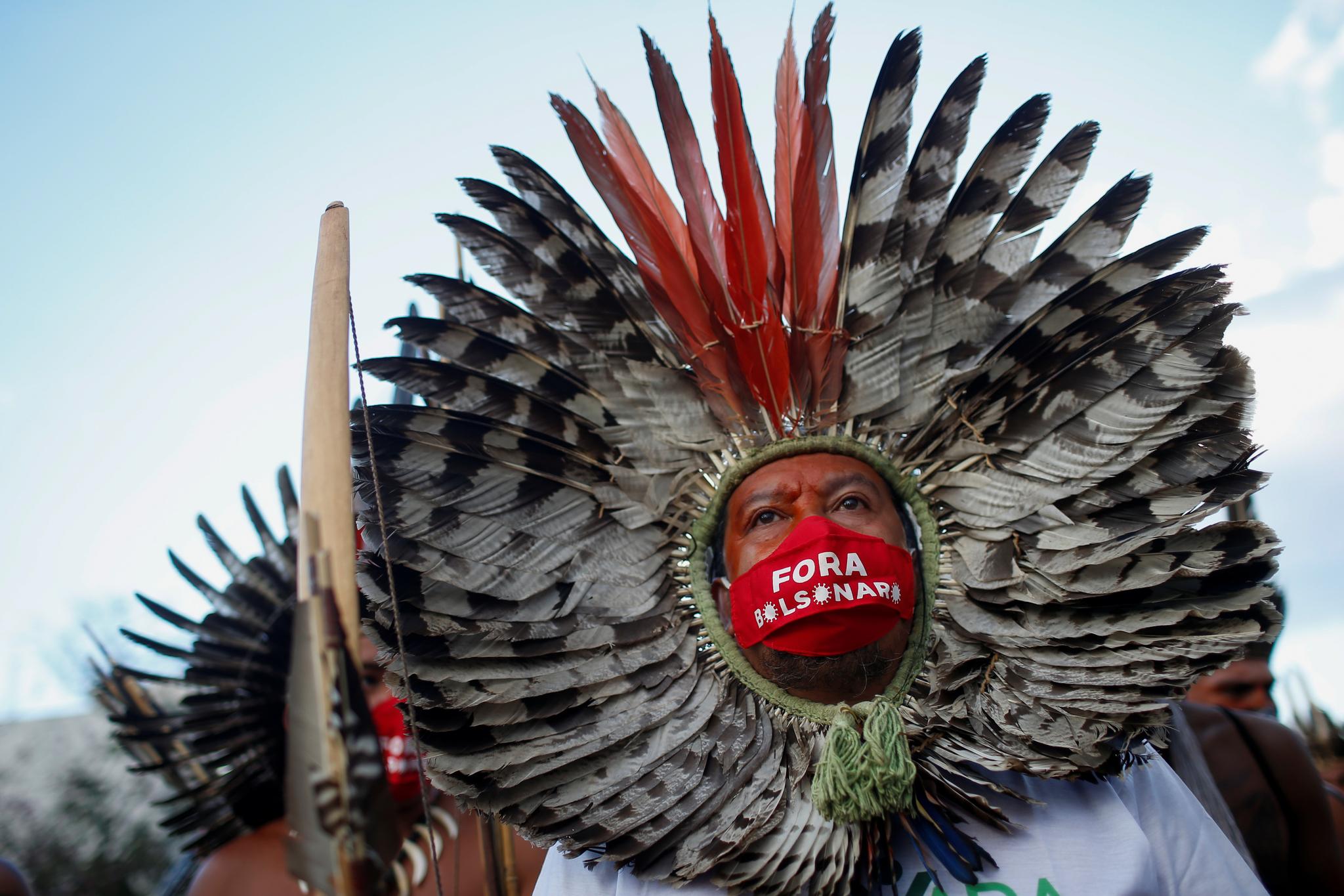 브라질 원주민들이 13일 코파 아메리카 개막전이 열리는 브라질리아 마네 가힌샤 스타디움 밖에서 '보우소나루 퇴진' 글씨가 새겨진 마스크를 쓰고 시위를 벌이고 있다. 이들은 코로나 19의 대유행 속에서 축구대회를 여는 것을 반대하고 있다. 로이터=연합뉴스
