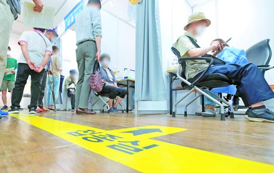 지난 12일 서울 강동구 예방접종센터에서 시민들이 백신 접종을 하고 있다. [연합뉴스]