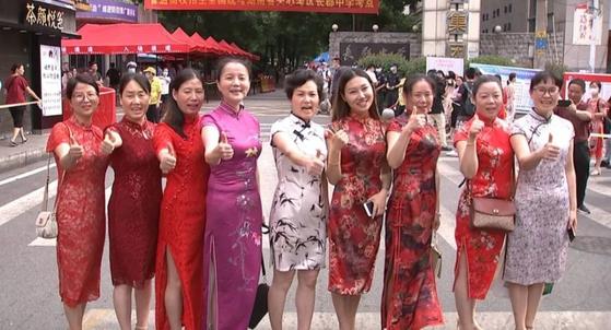 중국 후난성 창사의 엄마들이 지난주 대학 입시인 '가오카오' 시즌이 시작되자 '치파오'를 입고 수험장 앞에 나와 자녀들의 선전을 기원하고 있다. [중국 텅쉰망 캡처]