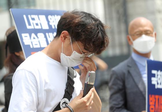 천안함 생존자 함은혁씨가 14일 서울 강남구 휘문고등학교 앞에서 천안함 사건과 관련해 욕설 등을 한 해당 고등학교 교사 A씨를 규탄하는 기자회견에 참석해 발언도중 눈물을 삼키고 있다. 뉴스1