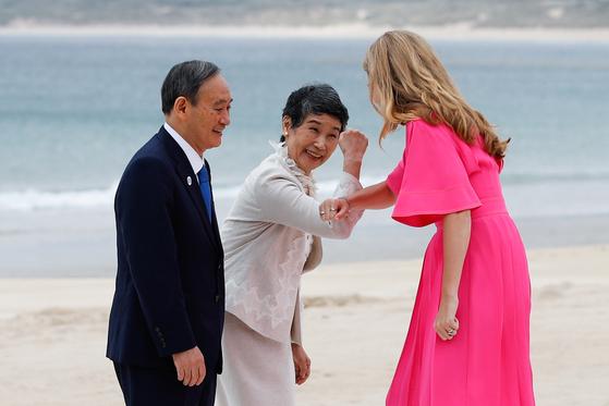 스가 총리(왼쪽)의 부인 마리코(가운데) 여사가 영국 총리 부인 캐리 시먼즈(오른쪽)와 인사를 나누고 있다. 로이터=연합뉴스
