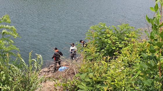 지난 13일 쇠줄이 허리에 묶힌 상태의 변사체가 발견된 충남 청양군의 한 저수지에서 경찰 과학수사요원이 수색작업을 벌이고 있다. 신진호 기자