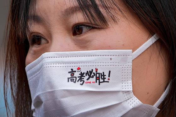 중국의 한 학부모가 자녀가 대입 시험에서 좋은 성적을 거두기를 바라는 마음에서 '가오카오 필승'이란 마스크를 쓰고 있다. [AP=연합뉴스]
