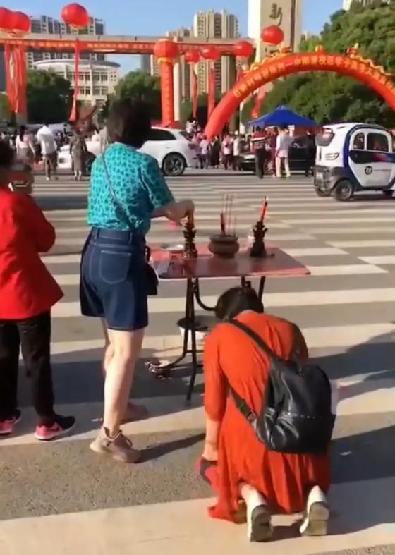 중국의 한 학부모가 후베이성 우한의 한 '가오카오' 수험장 앞에 제단을 차려놓고 향불을 피우며 자녀의 선전을 기원하고 있다. [중국 텅쉰망 캡처]