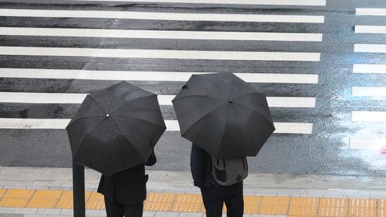지난달 25일 오전 서울시 중구 태평로에서 시민들이 우산을 쓰고 출근하고 있다. 연합뉴스