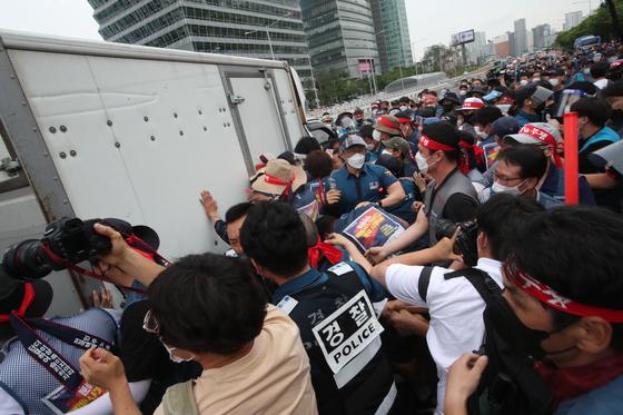 전국택배노동조합이 15일 서울 여의도 공원에서 1박2일 동안의 '서울 상경 투쟁'을 벌이고 있다. 이날 택배 노조원들이 도롯가에 정차중이던 트럭을 향해 기습 행진해 앰프 등의 장비를 내리고 있다. 우상조 기자