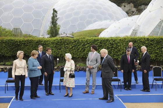 영국 엘리자베스 여왕과 사진촬영을 마친 G7 정상들이 환담하는 가운데 스가 총리가 뒤쪽에 서 있는 모습. [AP=연합뉴스]