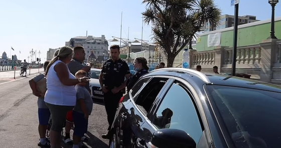 부부가 차량 뒷좌석 유리창을 깨고 개를 구조한 경찰에 항의하고 있다. 전체 장면은 아래 영상에 있다. [유튜브 캡처]
