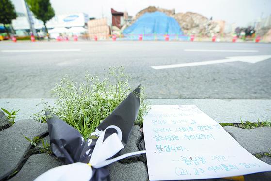 광주 동구 학동4 재개발 구역 철거 건물 붕괴 사고 현장 건너편 도로에 사망자를 추모하는 꽃다발과 손편지가 놓여있다. 연합뉴스