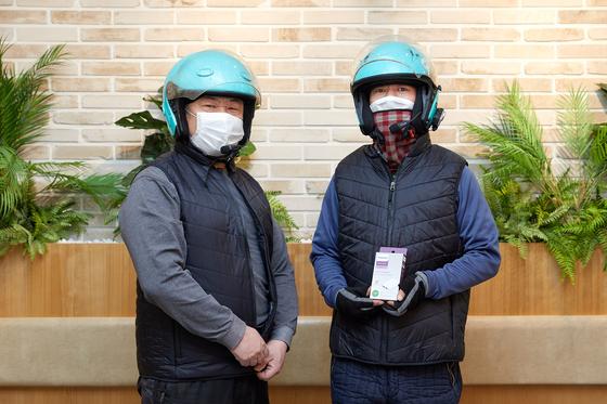 배민라이더스 및 B마트 서비스의 배달을 수행하는 라이더들이 발열조끼를 착용하고, 함께 지급된 조끼 온도 조절용 보조배터리를 들어 보이고 있다. [우아한형제들 제공]