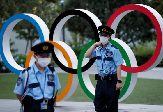 지난 14일 일본 도쿄 올림픽 경기장 인근에 있는 오륜 조형물 앞을 경비회사 직원들이 지키고 있다. [로이터=연합뉴스]
