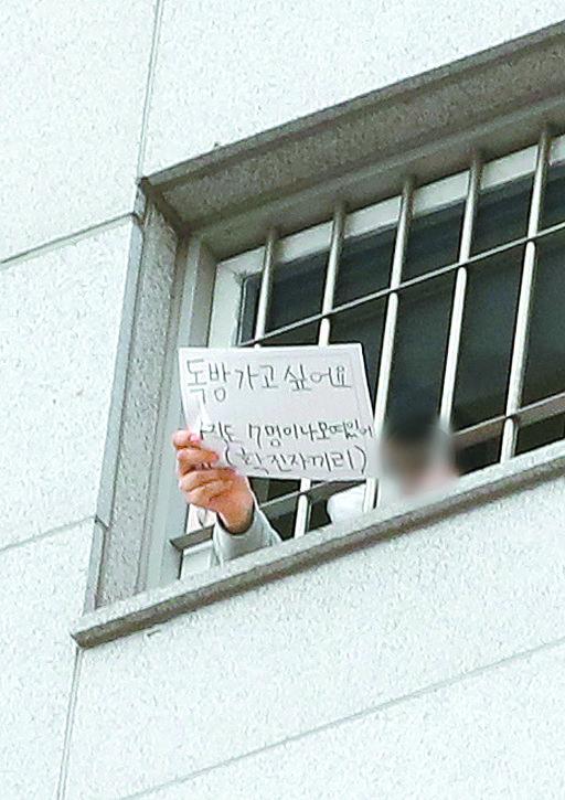 지난 1월 서울 송파구 동부구치소에서 한 재소자가 열악한 환경에 대한 문구가 적힌 글을 들어 보이고 있다. 뉴스1