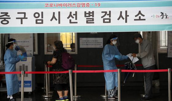 18일 오전 서울 중구 서울역광장에 마련된 신종 코로나바이러스 감염증(코로나19) 임시 선별검사소를 찾은 시민들이 검사를 위해 안내 받고 있다. 뉴스1