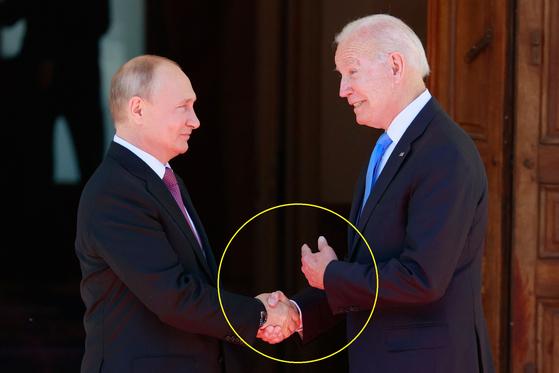 조 바이든 미국 대통령(오른쪽)과 블라디미르 푸틴 러시아 대통령이 16일(현지시간) 스위스 제네바의 정상 회담장에 도착해 악수하고 있다. 바이든 대통령은 이날 푸틴 대통령에게 먼저 악수를 청했지만, 악수가 끝나기도 전에 반대 손으로 회담장 안에 들어 가자는 제스처를 취했다.[AFP=연합뉴스]
