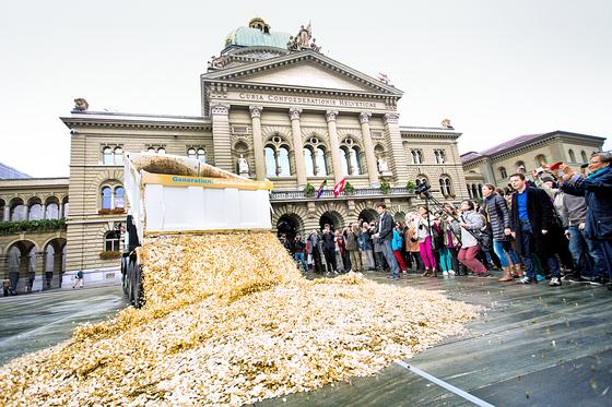 스위스 헌법에 기본소득 조항을 넣어야 한다고 주장한 운동가들이 국민투표에 필요한 12만5000명의 서명을 확보하고 이를 기념해 2013년 10월 4일 베른에서 기본소득을 상징하는 동전을 쏟아붓는 퍼포먼스를 하고 있다. 2016년 6월 5일 국민투표에서 76.9% 유권자들이 기본소득 도입에 반대했다. [사진제공=스테판 보러]