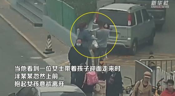 지난 4월 중국 텐진시 거리에서 한 남성이 엄마와 함께 걷고 있던 여자 아이를 들쳐 안고 달아나려고 하고 있다. [신화사]