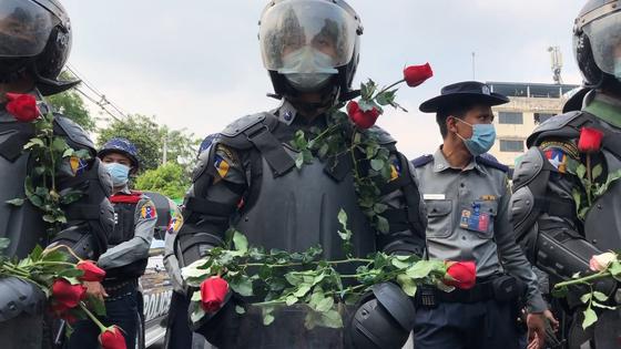 미얀마 군부 쿠데타에 맞선 민주화운동 현장을 담은 다큐멘터리 '버마 스프링 21' 한 장면. 유혈 폭력 사태가 벌어지기 전인 지난 2월 시위 초기엔 시위대가 군부의 군대, 경찰에 평화를 상징하는 장미꽃을 음식, 마실 것과 함께 건네며 비폭력 저항을 했다. [사진 한나 훔트, 버마 스프링 21]