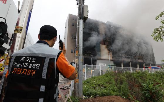 18일 오전 경기도 이천시 마장면 쿠팡 덕평물류센터 화재 현장에서 한 소방관이 무전을 주고받고 있다. 연합뉴스