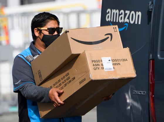 지난 2월 미국 캘리포니아주 호손시에서 아마존 배달 직원이 상품을 옮기고 있다.[AFP=연합뉴스]