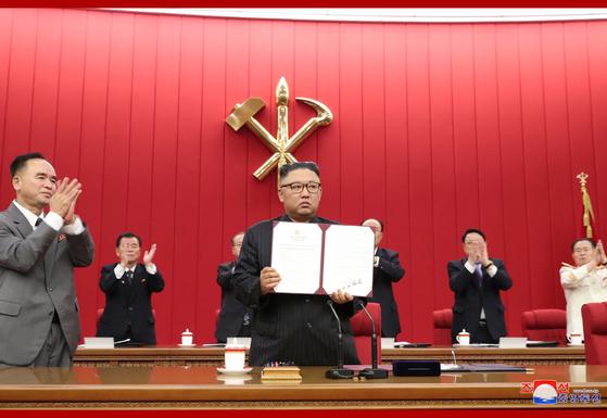 김정은 북한 국무위원장이 지난 17일 노동당 8기 3차 회의 셋째날 본인이 서명한 '특별명령서'를 들어 보이고 있다. [조선중앙통신=연합뉴스]