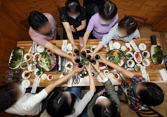 광주에서 사적 모임이 8명까지 가능해진 18일 오후 광주 북구청 인근 식당에서 북구청 공무원들이 지역 상권 활성화를 위해 구내식당에서 벗어나 오랜만에 8명이 모여 식사를 하며 음료수로 건배를 하고 있다.연합뉴스