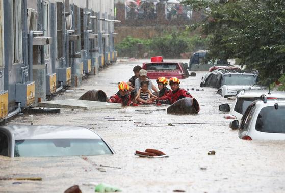 지난해 7월 30일 오전 대전시 서구 정림동 한 아파트 주차장과 건물 일부가 잠겨 주민들이 119 구조대의 도움을 받아 아파트에서 빠져나오고 있다. 연합뉴스